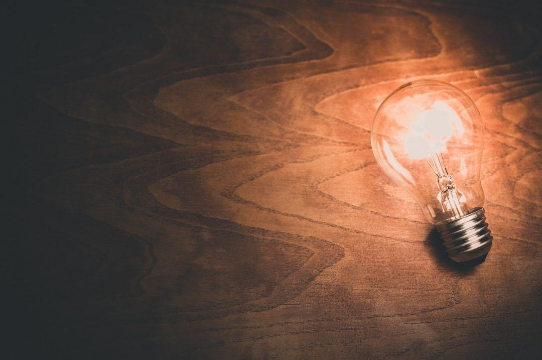Innovation mangement, lampadina accesa su piano di legno